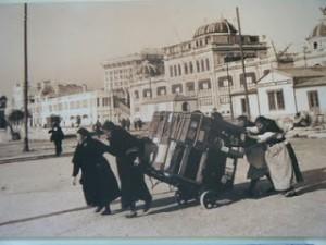 """Fuente: colecc. Ángel Blanco. """" Mujeres acarreando equipajes en el puerto de Coruña"""", 1925"""